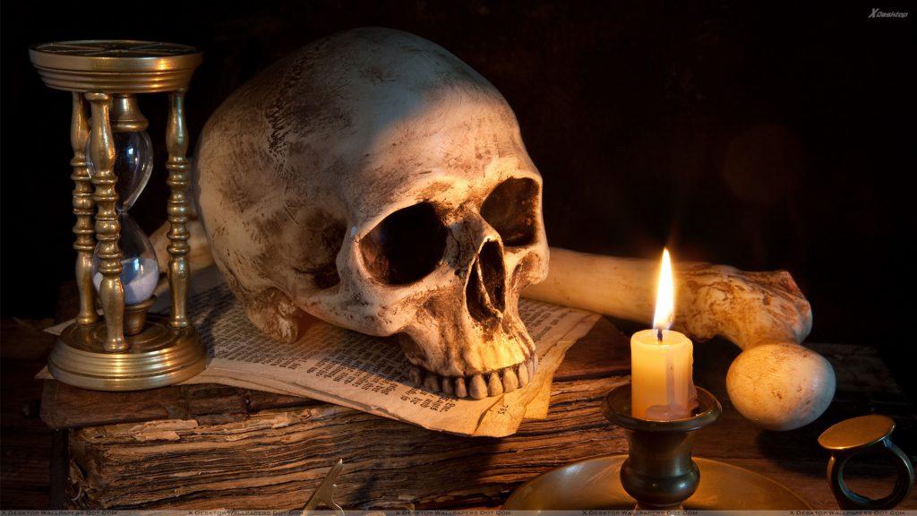 Череп лежит на старой книге, песочные часы,  горящая свеча, темнота
