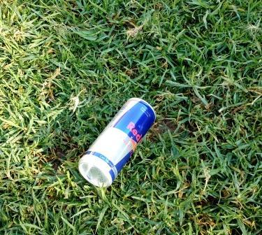 Банка Ред Бул на траве. Усталость не проходит.