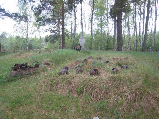 Братское захоронение, пробитые каски на траве